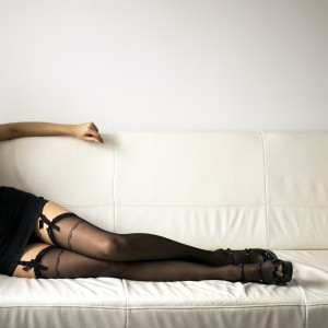 Long sexy Woman legs in black stockings on sofa, with high heels. Erotic pose