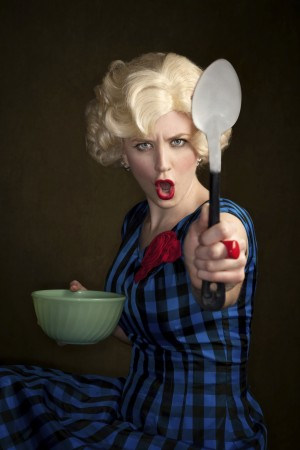 Pretty retro blonde woman in vintage 50s dress with bowl and spoon