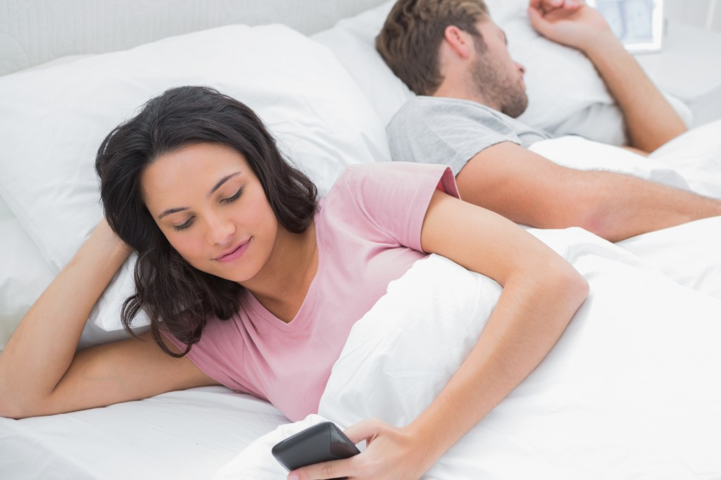 Woman using her phone while her husband is sleeping