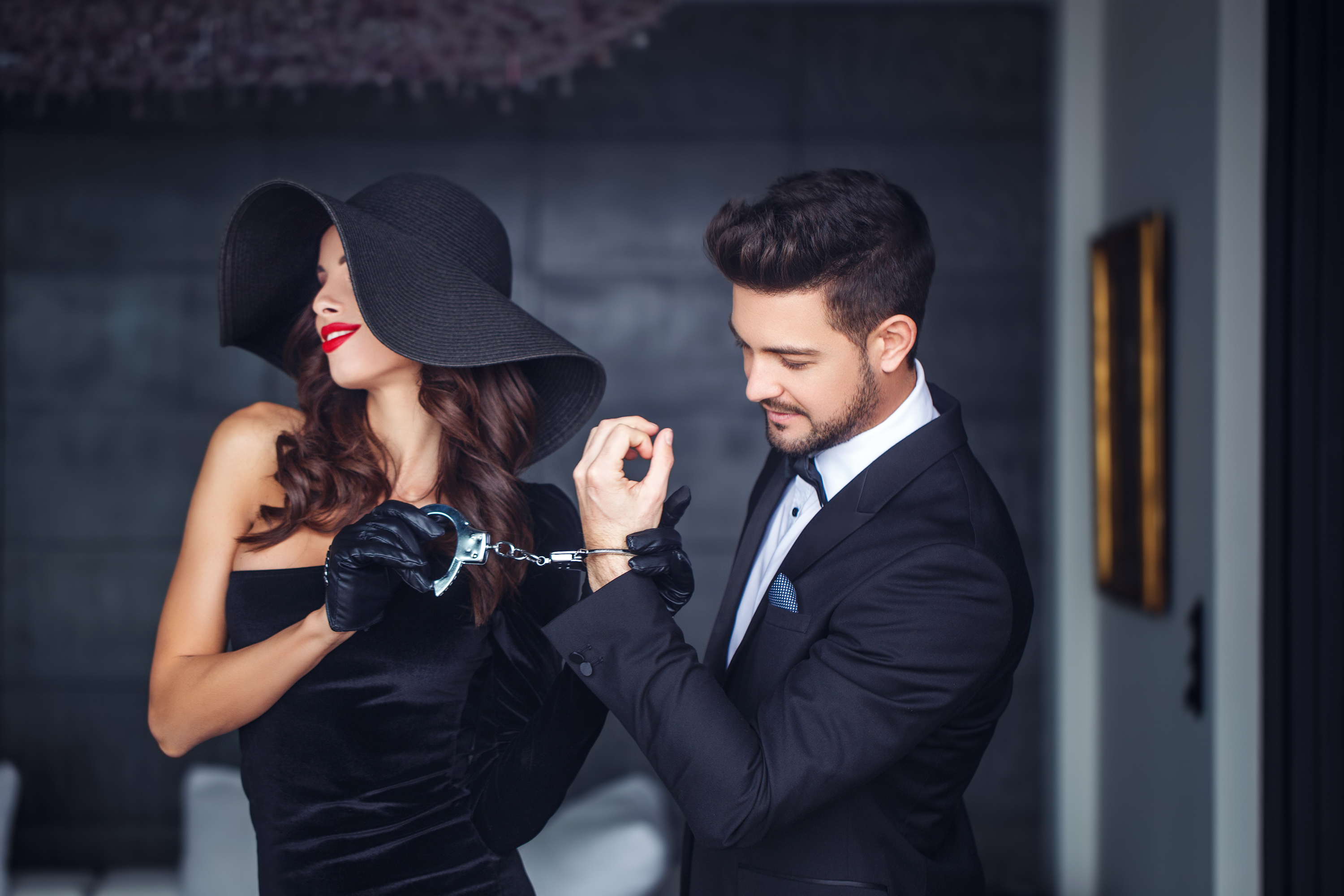 Woman in hat holding young man on handcuffs indoor