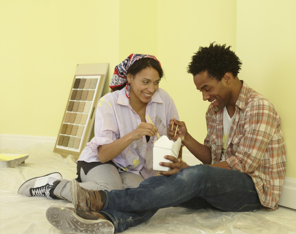African couple eating take-out in freshly painted room