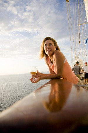 Woman holding a glass of wine on a sailboat, Tahaa, Tahiti, French Polynesia