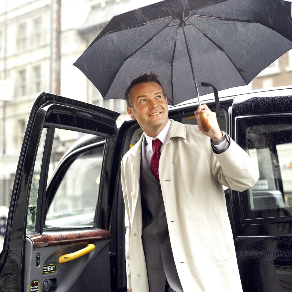 a man stepping out of a taxi with an umbrella