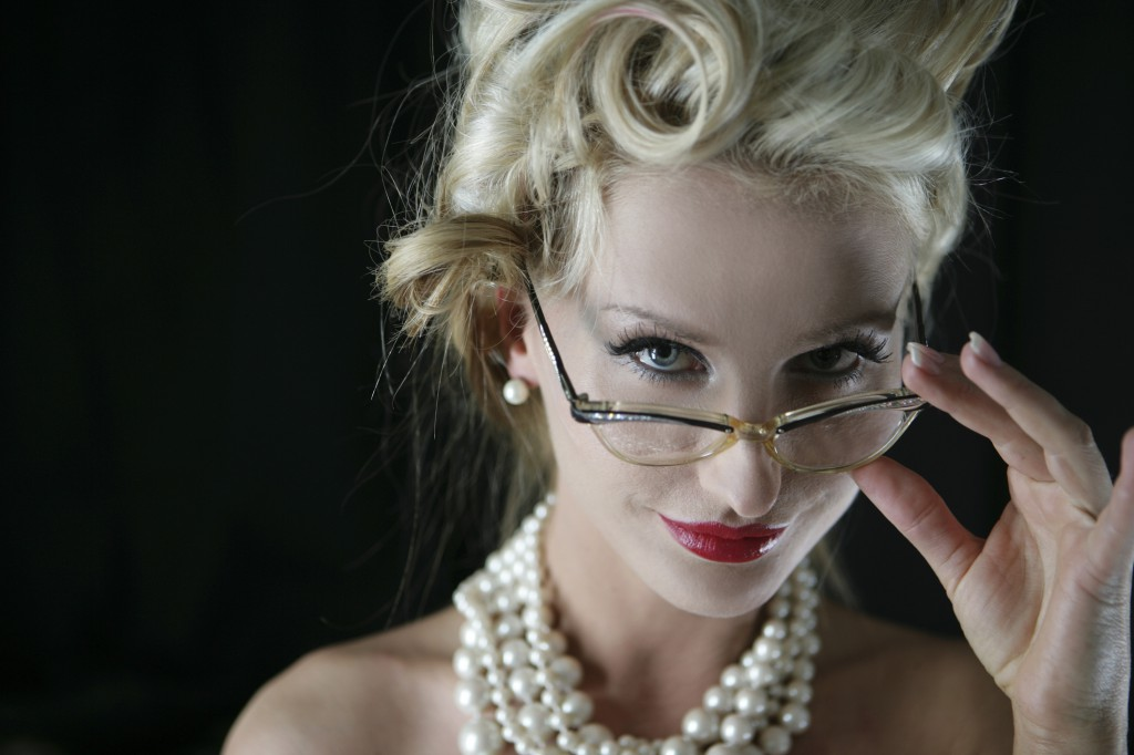 Portrait of sexy blonde woman in eyeglasses and pearl necklaces