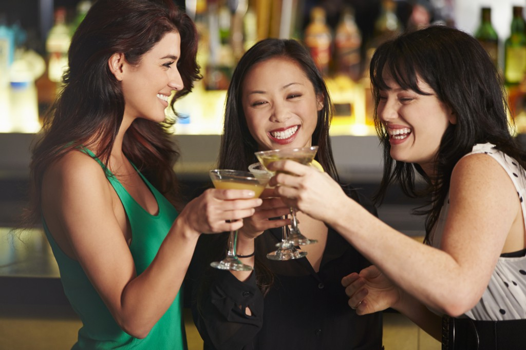 Three Female Friends Enjoying Drink In Cocktail Bar