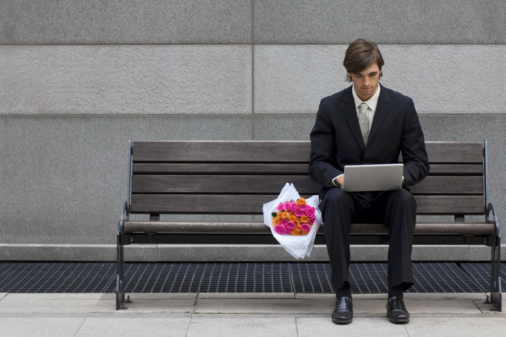 Man with bouquet using laptop computer