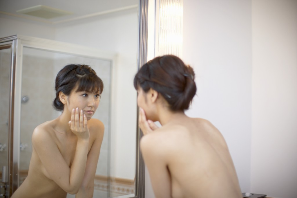 Young woman looking in bathroom mirror, close-up