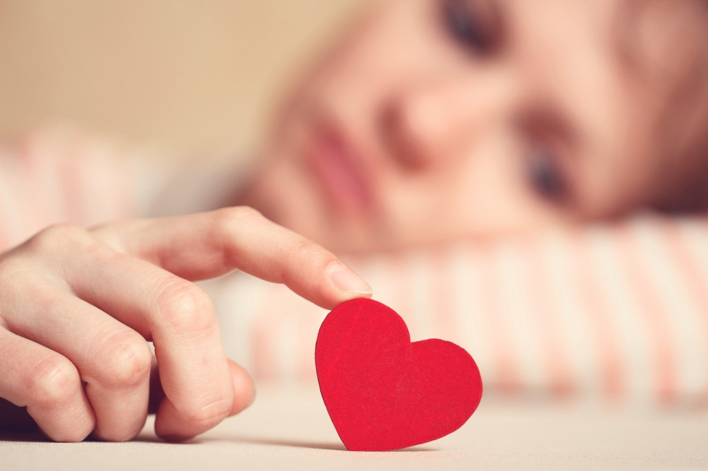 Sad girl is holding heart symbol by her finger