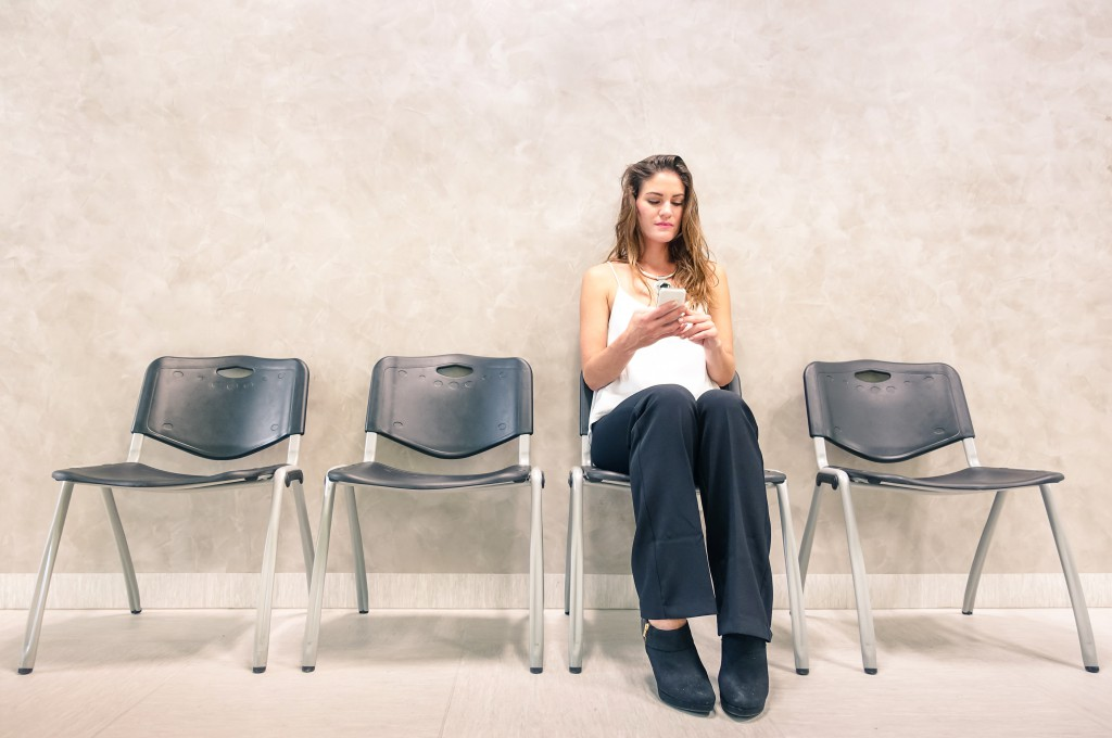 Pensive woman with mobile smart phone sitting in waiting room
