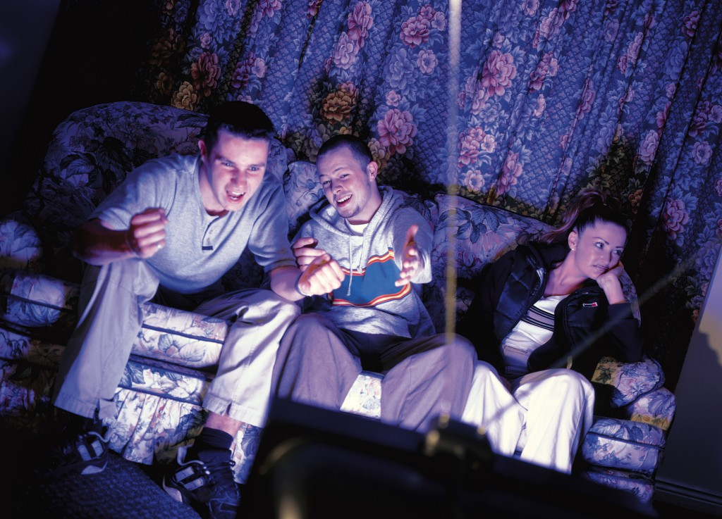 three young people sitting on a couch watching television