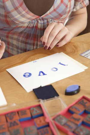 Young woman using letterpress stamps to create message