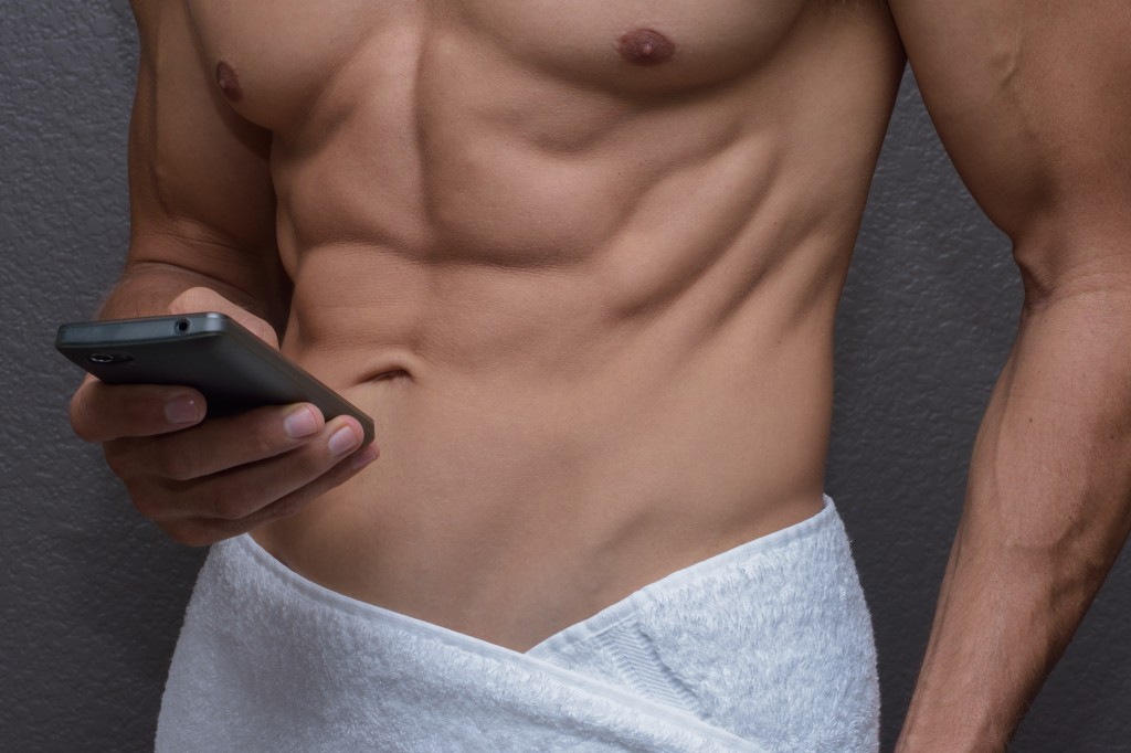 Closeup abs of man wrapped in towel as he texts