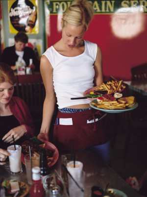 a blonde waitress delivers a meal to her customers
