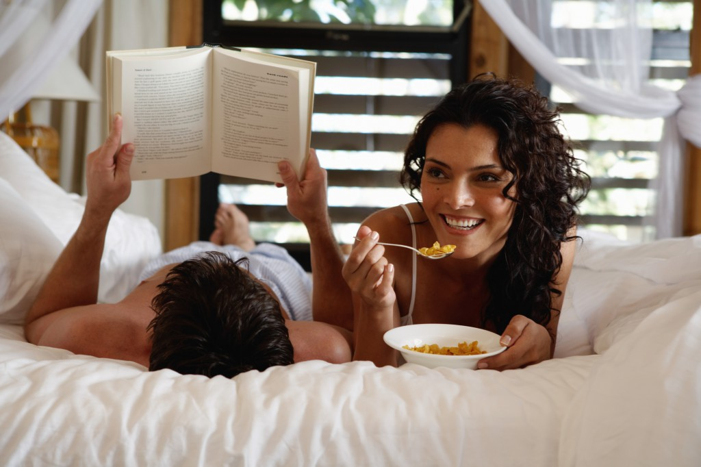 Woman with cereal bowl in bed, man reading, smiling, close-up