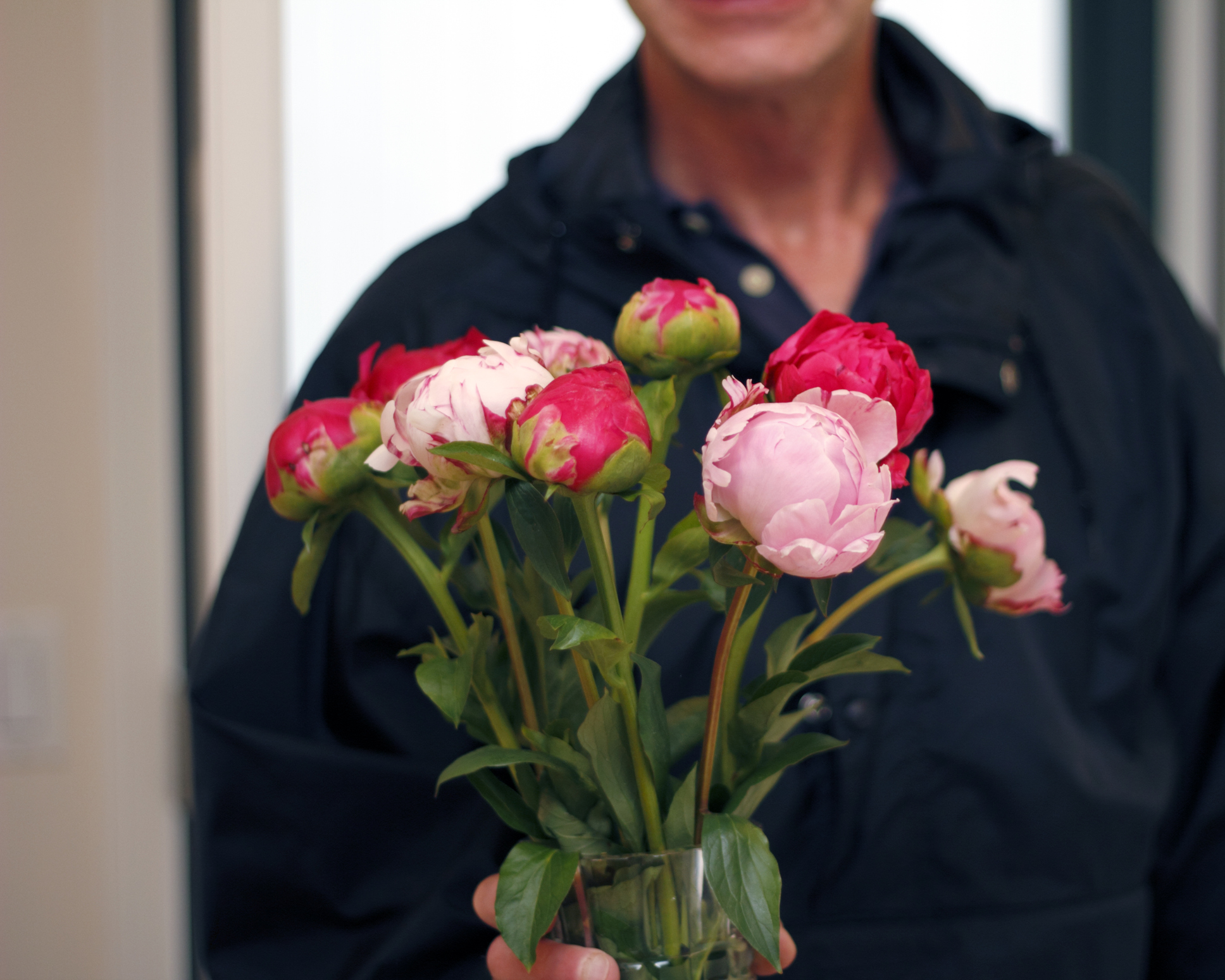 Man Giving Vase of Peonies