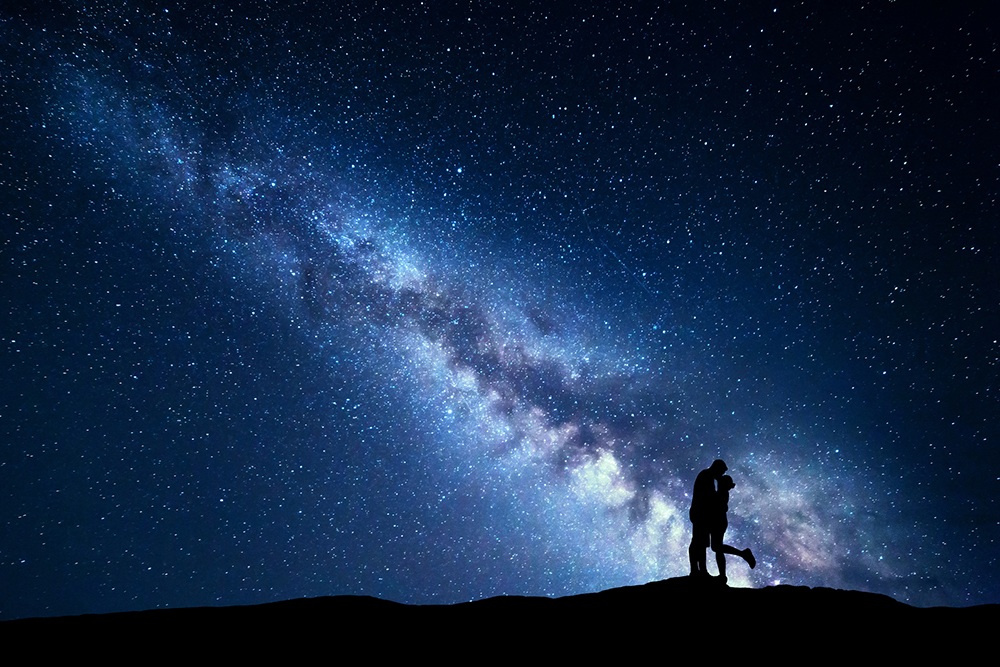Milky Way. Silhouettes of hugging and kissing man and woman