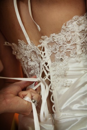 Bride having her dress laced up