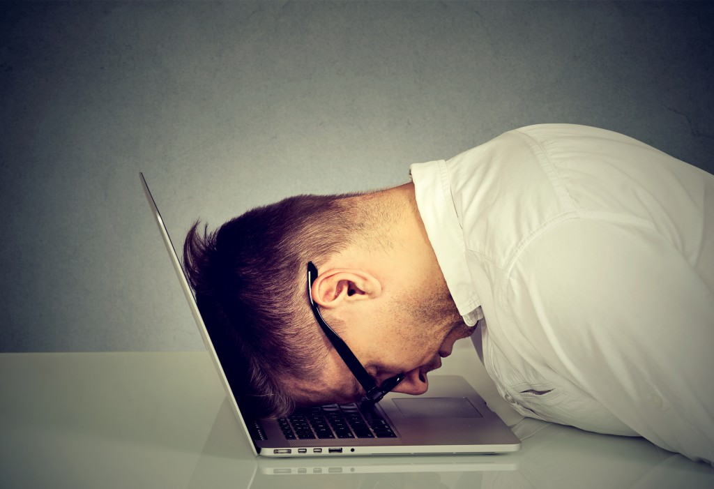 Desperate employee stressed man resting head on laptop