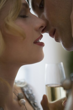 Close-up of young couple with champagne about to kiss