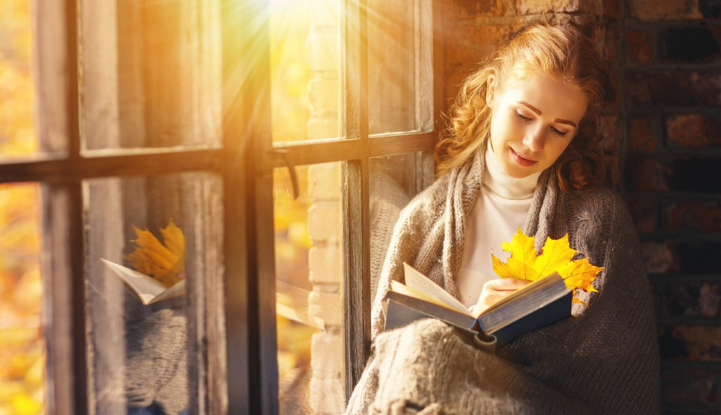 Happy young woman reading book by window in fall